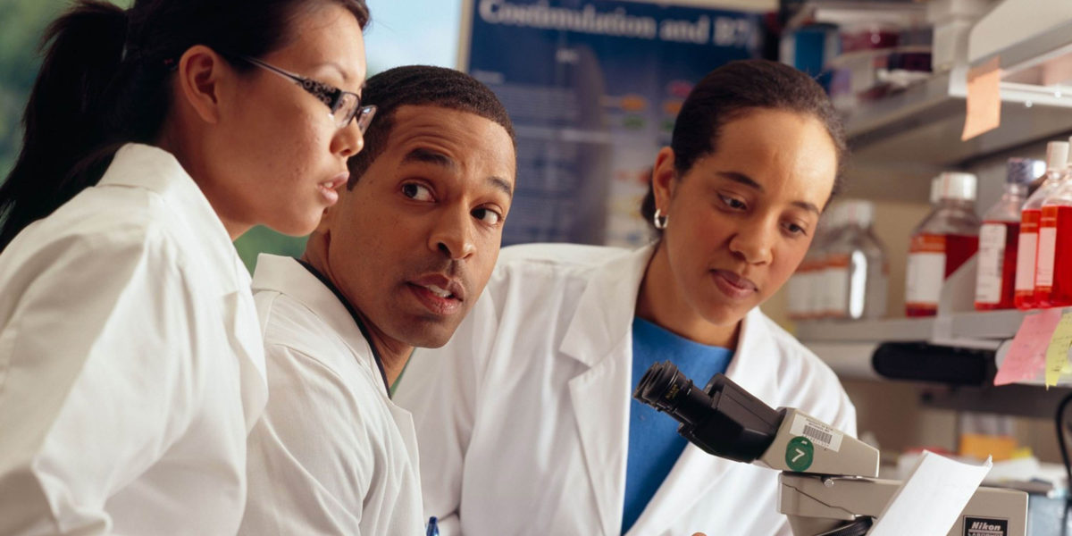 Three researchers in white coats at a microscope.