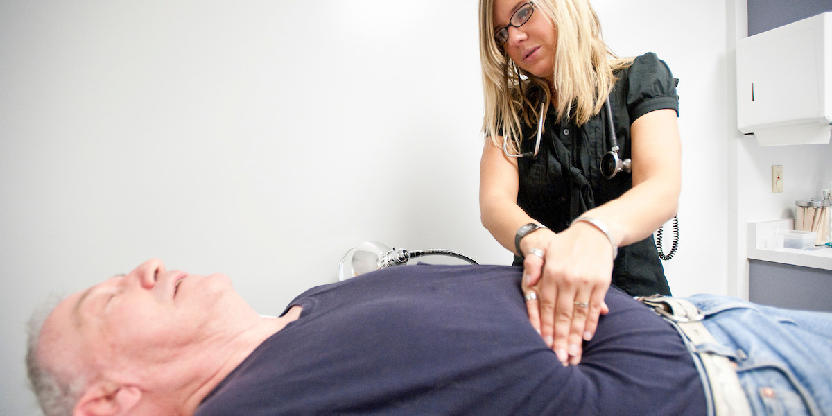 Health Professional palpating a patients stomach.