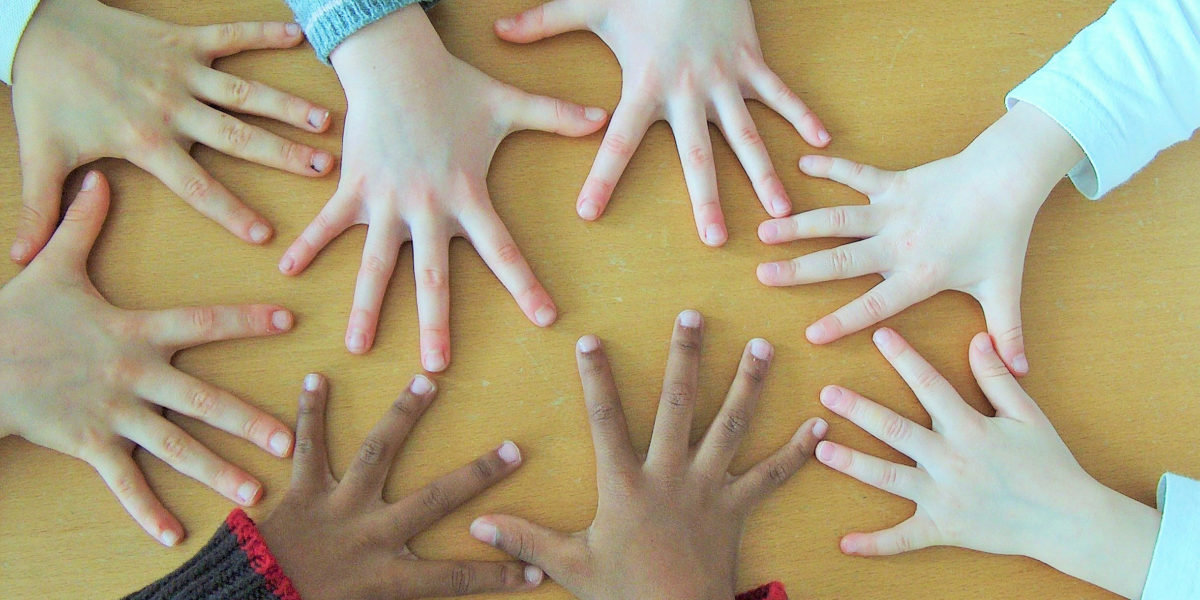 Children's hands of different skin tones.